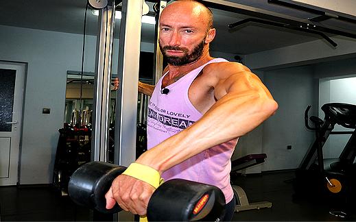 Да разширим раменете с разтваряне с дъмбел встрани с една ръка от опора